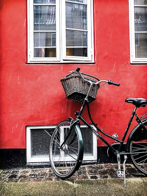 a bicycle with a red wall and white framed windows in Copenhagen, Denmark