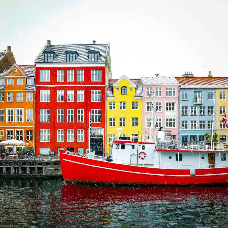 Beautifully coloured buildings and a red boat in Nyhavn, Copenhagen, Denmark