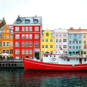 a boat and colourful buildings in Nyhaven, Copenhagen, denmark