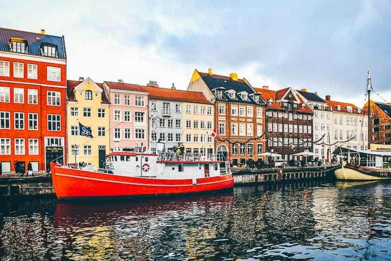 A red boat and colourful buildings in Nyhavn, Copenhagen, Denmark