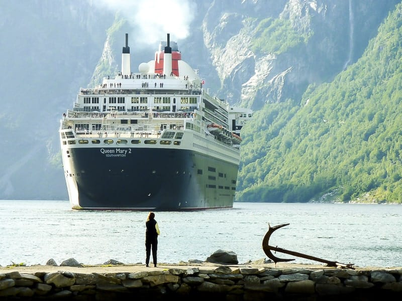 a woman looking at Queen Mary II in Norwegian Fjord.