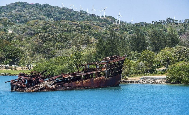 Half sunken wreck ship floating in the water at Mahogany Bay Roatan Honduras