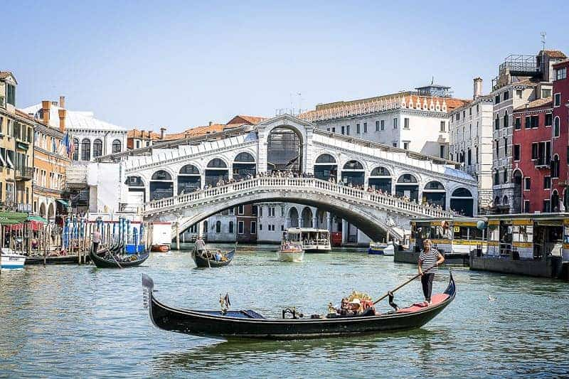 The Rialto Bridge with a gondola in Venice, Italy